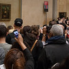 Crowds at the Mona Lisa.  The sign on the right warns visitors to watch out for pickpockets.