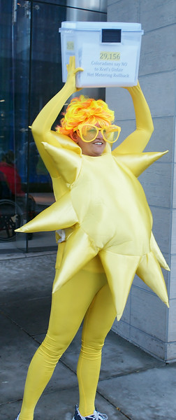 "Woman in ""sun"" costume holds box of petitions supporting rooftop solar energy, to be delivered to the offices of utility corporation Xcel Energy in Denver."