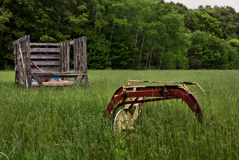 "Seemingly Abandoned23 May 2013 -- 143/365Johnston, Rhode IslandThe remains of a hay wagon and some farm equipment lay seemingly abandoned on the border of Dame Farm and Snake Den State Park.  Technically, the two overlap since the historic farm was is part of the state managed property when Snake Den was purchased from the Palazzi family in 1969.  The state plans to maintain this portion of the farm as a working farm to preserve Rhode Island's ""rich but diminishing agricultural heritage.""Despite the name, Snake Den is not associated with any of the reptiles that reputedly occupied much of the state.  Rather, it's named for a canyon-like fissure that is a remnant of the state's glacial past.  The 1000 acre park has numerous hiking trails that were sparsely marked the last time I wandered through the area.  Some of the trails lead to this field, although the abundance of deer ticks (and the accompanying threat of Lyme Disease) in the area has reduced the number of summer visitors significantly.Post processing started with a brilliant warm filter in Topaz Adjust.  I adjusted adaptive exposure, regions, contrast, and protect highlights.  A levels adjustment was added in PSE."