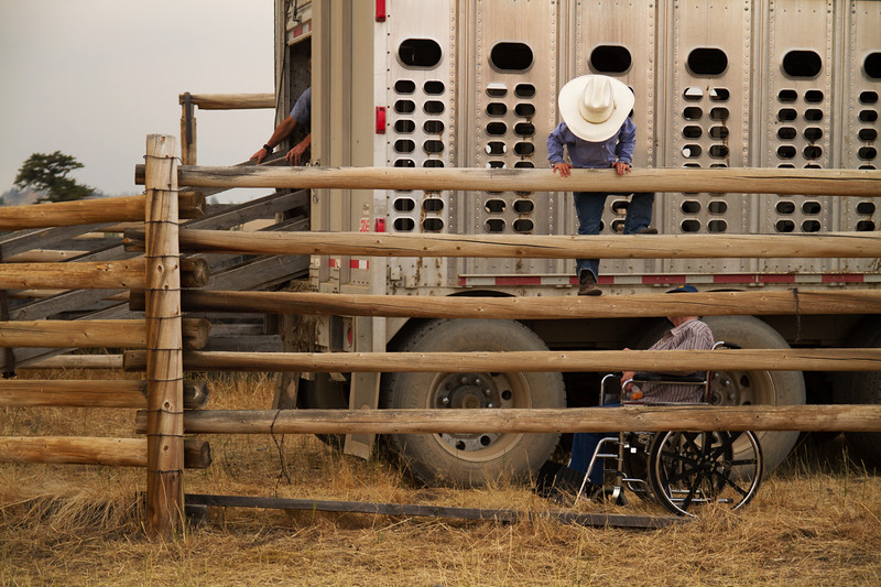 Granddaughter climbs a fence with a cowgirl hat after saying hello to her Grandmother in a wheelchair, as dad prepares the semi for sheep.