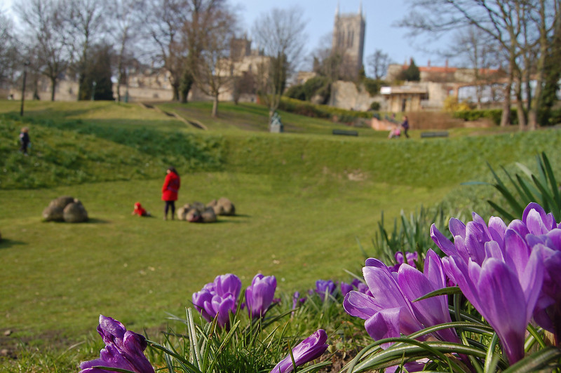 "09.04.13 - Spring in Temple Gardens  Spring sunshine on the crocuses, a family playing amongst the ""dinosaur poo"" sculpture, and the cathedral on the hill behind, idyllic? Well yes, apart from the biting east wind that still blights most of the UK. But at least it has been dry for a couple of weeks now, which enabled me to lay on the ground to take this shot.  The wind is due to turn westerly tomorrow, so it will be warmer but wetter, what a trade off!"