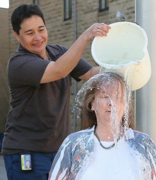 Domestic Relations Judge Lisa Swenski made a $250 donation to the ALS charity and challenged the other Lorain County judges to match her. Dumping the bucket is Diversion Specialist Mildred Gonzalez. BRUCE BISHOP/CHRONICLE