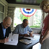 "Lorain County Historical Society secretary Robert Ebert left, and Director William Bird, co-authors of ""Elyria,"" sign copies for Patti Thomin of Elyria at The Lorain County Historical Society at The Hickories Museum in Elyria on Aug. 19. STEVE MANHEIM/CHRONICLE"