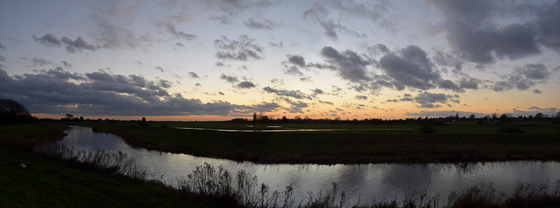 19.12.14 - Dusk<br /> <br /> The dog (white blob bottom left) and I missed the sunset last night, but the sky was still quite nice down by the river. This is a 2 shot photomerge panorama comprising the whole sky, south (left) to west (right). Over the river you can also see that the fields are flooded, this always happens at this time of year, the land is so low lying here. Only a couple more nights and the sun will start it's journey back north across the sky and the days will get longer again :)