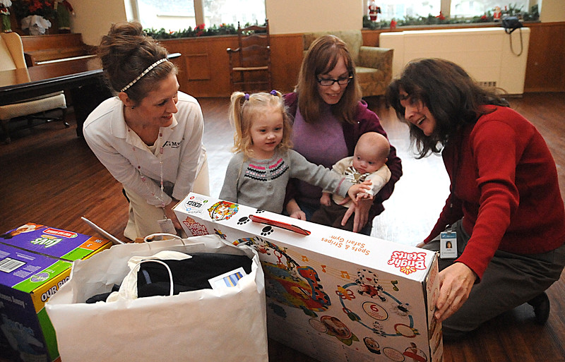 Heather Leonard, left, resource mother with of Mercy Regional Medical Center's Resource Mother's program, Melisa Miller with daughter Emma, 3, and son Hunter, 5 months old, and Emily Demyan, resource mother program coordinator, look at Christmas gift donations at Elyria YWCA on Dec. 18. STEVE MANHEIM/CHRONICLE