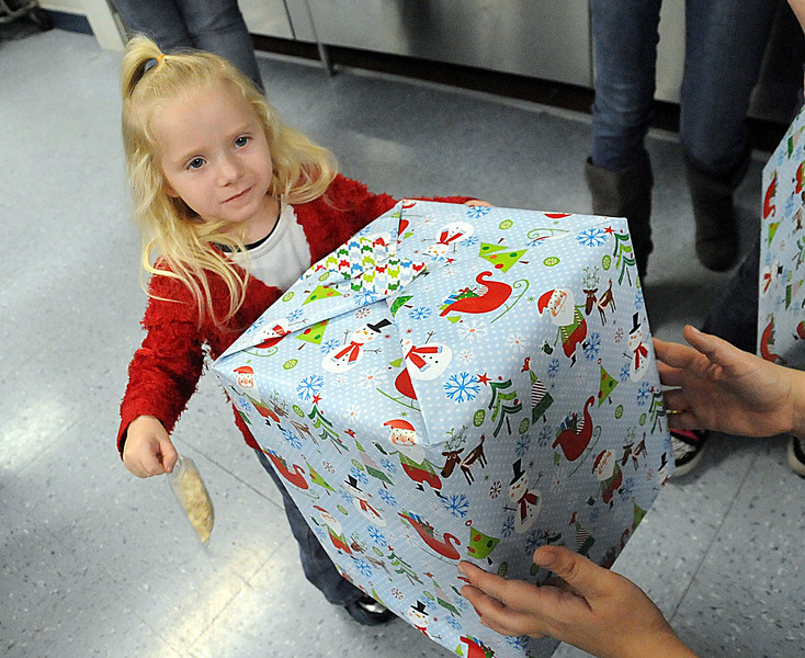 """Clairity Vance, 2, of Elyria, gets a Christmas present from Allison Baker of Cub Scout Pack 324 at """"Scout for Kids"""" program at Vincent Elementary in Sheffield Twp. on Dec. 18.  Cub Scout Pack 324 of Elyria raised over $1,200 in donations to purchase over 100 toys for 18 families in Lorain County in this community service project.  StSTEVE MANHEIM/CHRONICLE"""