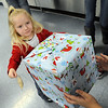 "Clairity Vance, 2, of Elyria, gets a Christmas present from Allison Baker of Cub Scout Pack 324 at ""Scout for Kids"" program at Vincent Elementary in Sheffield Twp. on Dec. 18.  Cub Scout Pack 324 of Elyria raised over $1,200 in donations to purchase over 100 toys for 18 families in Lorain County in this community service project.  StSTEVE MANHEIM/CHRONICLE"