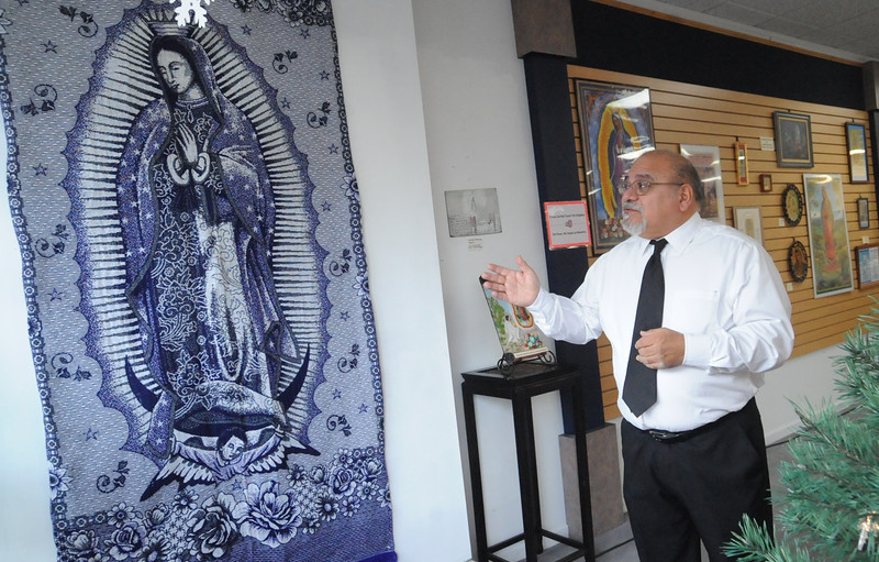Guillermo Arriage, president of the Museum of Hispanic and Latino Cultures, stands next to a tapestry at the museum's Virgin of Guadalupe Exhibit at Lorain Arts Council on Dec. 11.  Over 150 pieces of the patron saint Guadalupana were on display for the Feast of Our Lady of Guadalupe on Dec. 12.  STEVE MANHEIM/CHRONICLE