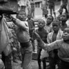 ANGOLA. Town of Luena. Moxico District. Children waiting for P.A.M. to hand out food. They collect pieces of corn falling out of the sacks. 1994.