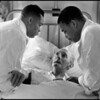 G.B. ENGLAND. Midlands. An elderly white patient wakes up in hospital to find two black male nurses tending him. 1969.