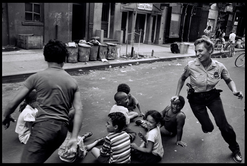 USA. New York City. 1978. A policewoman plays with local kids in Harlem.