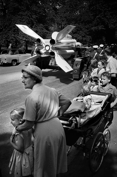 GB. ENGLAND. 1960. Nanny watching Military Parade passing down the Mall. Armed forces are always eager to brandish their latest purchases, by which some members of the public are possibly reassured.