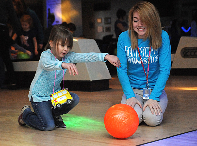 Pre-school student Abby Jonts bowls with Abbie Whitman, a Lorain County JVS early childhood education student, from LaGrange, at a bowling furndraiser at Strikeout Lanes in Wellington Jan. 27.  STEVE MANHEIM/CHRONICLE