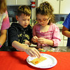 "Madeline Dean-Dielman and Robbie Castro, of Amherst, place candies on a graham cracker in an assembly line demonstration at the ""History Through Young Eyes"" program at Amherst Sandstone Village on July 17. STEVE MANHEIM/CHRONICLE"