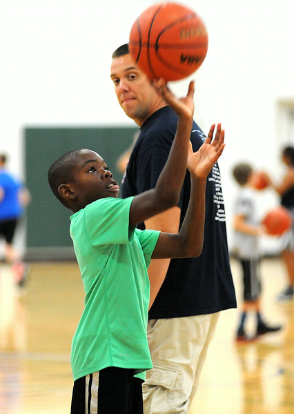 Elyria firefighter Mark Slack instructs Elisha Fisher, 10, of Elyria, in free-throw shooting at the Reach and Rise Elyria Firefighters Basketball Camp at Elyria South Recreation Center on July 28.  The firefighters' weeklong camp is designed to foster one-on-one relationships with Elyria youth, while teaching basketball fundamentals, sportsmanship and teammwork. STEVE MANHEIM/CHRONICLE