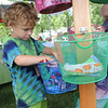 Steven Alten, 6, of Bay Village, looks through items at Emmie's Handmade clothing of Bay Village, at the ninth annual Summer Market at Veteran's Memorial Park in Avon Lake on July 25. The market features vintage, handmade and beach-themed wares, including furniture, art, clothing, fresh produce, home docor and antiques.  The market continues Sat. from 9 am to 5 pm. STEVE MANHEIM/CHRONICLE