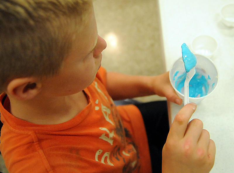 Owen Keller, 12, of Elyria, mixes borax, corn starch, hot water and glue to make a bouncy ball at the Mad Science Camp at East Recreation Center on July 23.  STEVE MANHEIM/CHRONICLE