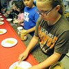 "Lyndsey Harpst, right, of Elyria, spreads peanut butter on a graham cracker to pass on to Gage Cohoon, of Amherst, in an assembly line at the ""History Through Young Eyes"" program at Amherst Sandstone Village on July 17. STEVE MANHEIM/CHRONICLE"