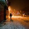 New York Winter Night - East Village Graffiti and Snow - By Vivienne Gucwa  A person walks down a sidewalk covered in snow next to a storefront covered in graffiti in the East Village, a neighborhood in lower Manhattan as snow falls and blankets New York City at night.  ---