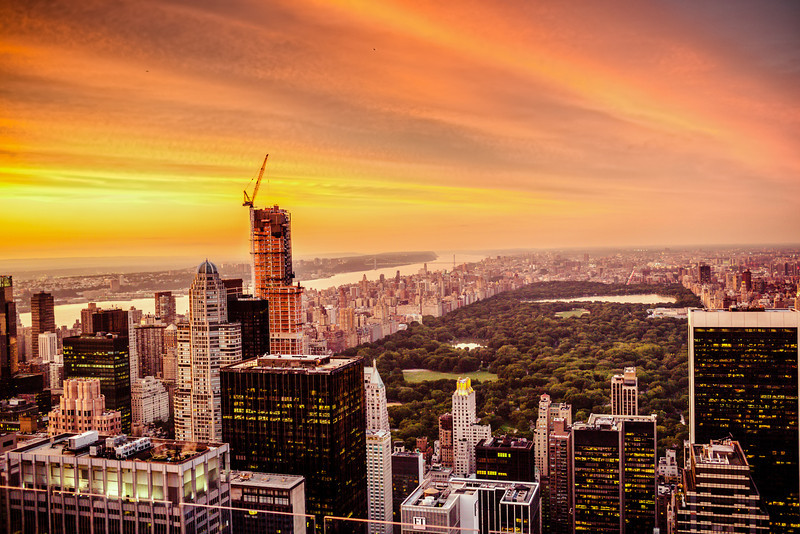 New York City Skyline and Central Park - Sunset  - By Vivienne Gucwa  Summer evenings are when the city smolders  as the sun paints the clouds  and the night sky waits just another hour longer  to dance with the last remnants of the day.  ---  This is a view of the skyscrapers of midtown Manhattan and Central Park from above looking north towards upper Manhattan. I took this at the end of August on a gorgeous, sweltering evening. I made it up to the top deck of Top of the Rock (30 Rock) just as this spectacular sunset was making its way across the sky. It's hard not to feel overcome with emotion when the summer sky puts on one of its late summer sunset shows. When it happens, the city is bathed in an other-worldly glow as the lights in the buildings twinkle on like stars and the sky and the impossible all seem to melt away into an infinite horizon full of endless possibility.  ---