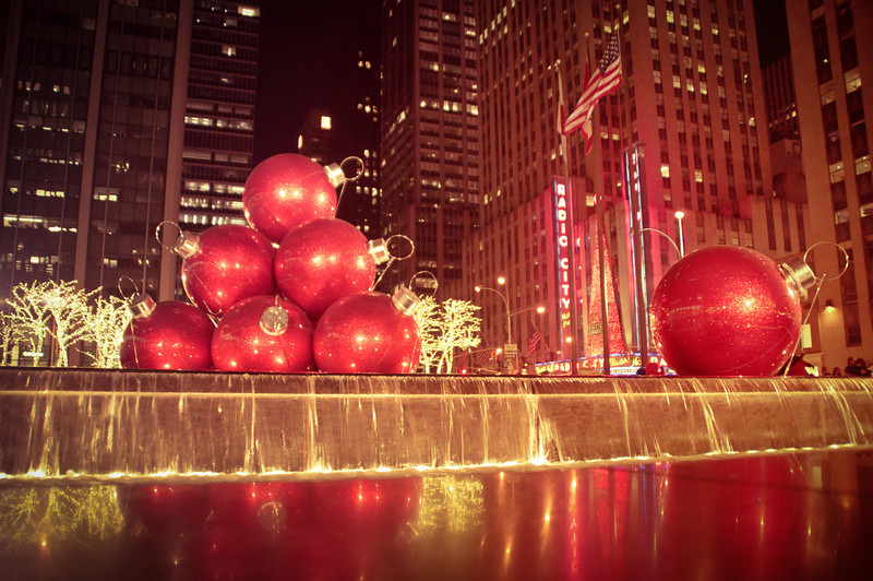 Giant Red Ornaments on 6th Avenue - Midtown Holiday Decorations - New York City - By Vivienne Gucwa  This display close to Rockefeller Center is a New York City holiday decoration extravaganza. It sits across from Radio City Music Hall (home of the Rockettes and Radio City Christmas Spectacular) on 6th Avenue and is absolutely gorgeous at night. Giant red ornament balls sit on a fountain which is surrounded by trees ensconced in holiday lights.  ---