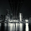 <h2>Under the Ed Koch Queensboro Bridge - New York City</h2> - By Vivienne Gucwa<br><br>  I had a recurring dream when I was younger that puzzled me for years. It involved boarding a hovering bubble shaped vehicle and ascending over the skyscrapers until I was soaring under the bridges and through the cavern-like spaces of the city. It was euphoric but also terrifying at the same time. When I was older, I finally relayed the dream to someone and they laughed and asked if I had ever taken the Roosevelt Island tram when I was very young. I had no recollection of it. It prompted me to ask my mother if we had ever done such a thing and she said it was possible but she couldn't remember a specific time that we would have done it (my mother, like me, is absolutely terrified of heights). It's possible that my family took the tram to Roosevelt Island at some point and the experience embedded itself deep into my imagination where it mixed with other flights of fancy (pun intended) of flying through a Gotham-like city like Batman.<br><br>  So, when I found myself photographing the underbelly of the 59th Street Bridge (also known as the Ed Koch Queensboro Bridge or just the Queensboro Bridge) late last week, it was hard not to recall those earlier dreams and feelings they invoked while I stood there waiting for the long exposure to capture 30 seconds of what had haunted me for years. The bridge is one of my favorite ones in the city. Its architecture is distinctive when viewed from the side but I absolutely love how slick and dripping-with-sci-fi-overtones it appears when viewed from below. The bridge travels from darkness into the light of a gleaming New York City as the water below it only stirs with the occasional disruption of a boat. You can also make out the cables that the Roosevelt Island tram travels on to the right of the bridge.<br><br>  ---<br><br>
