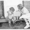 [Gloria Starkell and her sister blowing bubbles out of clay pipes]