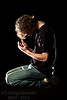 Young man kneels and prays
