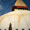 Tibetan performing a kora around the upper part of Boudhanath Stupa, Kathmandu Valley, Nepal (note the matching colors of person's clothes and temple)