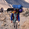 Porter with kitchen and live chicken leaving Paiju, Baltoro Glacier Trek, Karakoram Range, Baltistan, Pakistan
