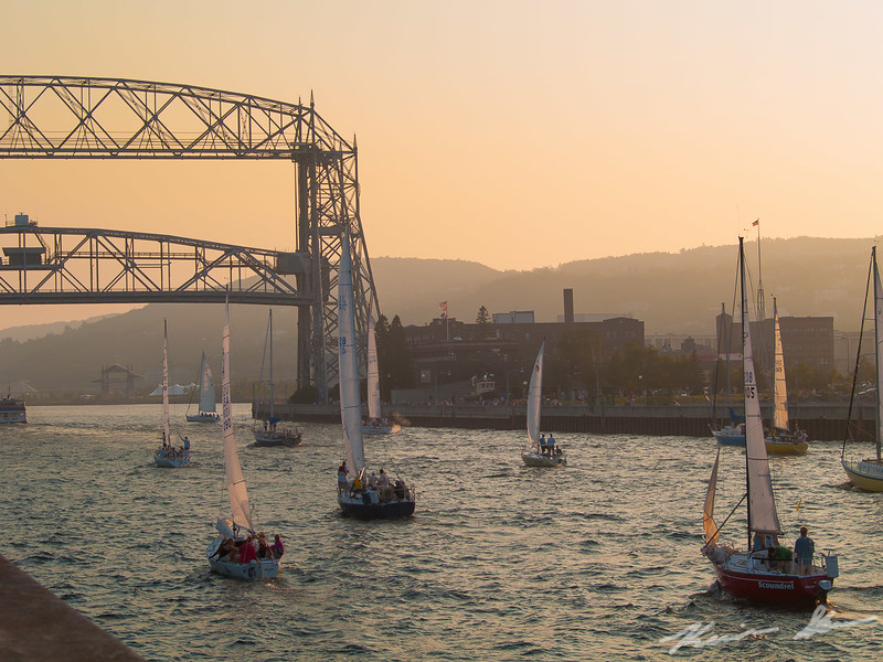 A parade of sailboats enter the canal after an afternoon on the lake