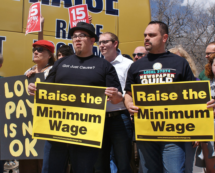 Two men at rally hold signs supporting raising the minimum wage, one wearing Newspaper Guild t-shirt, other demonstrators with signs behind them.