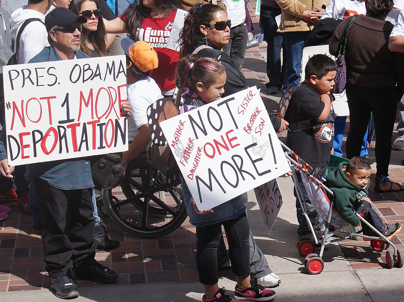 Hispanic mother and three children, one in stroller, one holding sign at immigration reform rally, man with sign behind them.