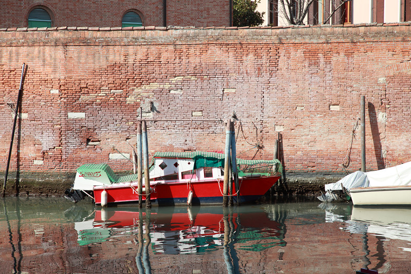 A red boat reflected in the water of a canal, The Jewish Quarter, Venice, Italy