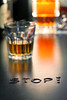 The word Stop with glass of  whiskey in background, shallow DOF