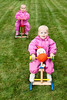 Two little baby girls wearing pink suits sitting on rocking horses outdoors