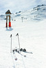Blank signpost and skis on piste at ski resort