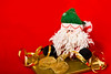 Christmas Santa puppet and the golden gift box with ribbon on red