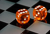 Two cube amber dice with rounded corners on checkered board