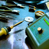 Soldering station with soft solder and  tools in background, shallow DOF