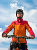 Portrait of adult cyclist on mountain bike against blue sky