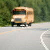 blurry abstract view of school bus driving on road
