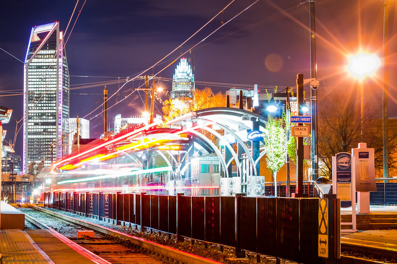 Charlotte City Skyline night scene with light rail system lynx train