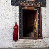 TRONGSA DZONG. MONK WAITING AT THE ENTRANCE GATE.