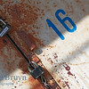 Number sixteen with old lock on white background with cracked paint and rust colors