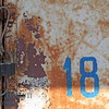 Number eighteen with old lock on white background with cracked paint and rust colors