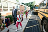 Grant Line Elementary Principal Kyle Lanoue walks with students as they disembark from busses on the first day of school in Southern Indiana.