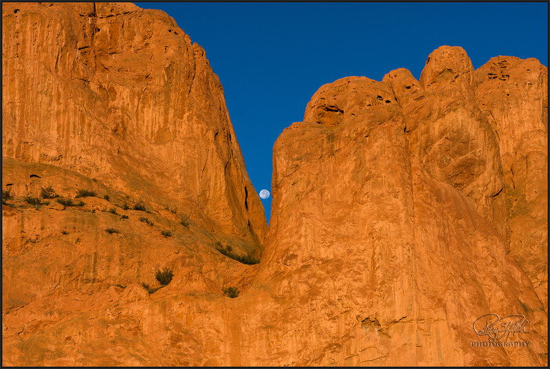 Garden of the Gods Moon.  I was in Colorado Springs and drove up for sunrise photos at the Garden of the Gods.  The full moon was setting at the time of the sunrise.  Getting the shot between the rocks took a lot of moving around and a lot of photos.  Amazing how quickly the moon moves.