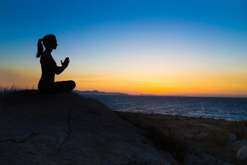 Silhouette of girl practiciing yoga on a rock