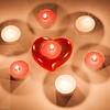 A display of candles centered around a heart for Valentine's day.